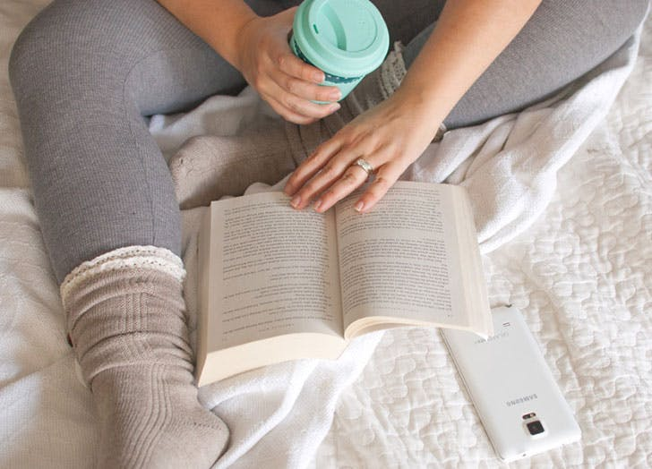 Girl sitting on bed with cup of coffee and reading