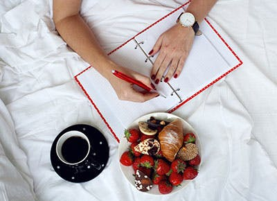 Woman writing down notes in bed with food