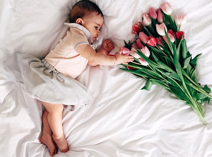Baby girl on bed with tulips