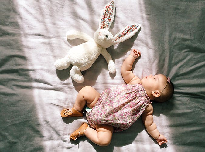Baby girl sleeping with stuffed rabbit