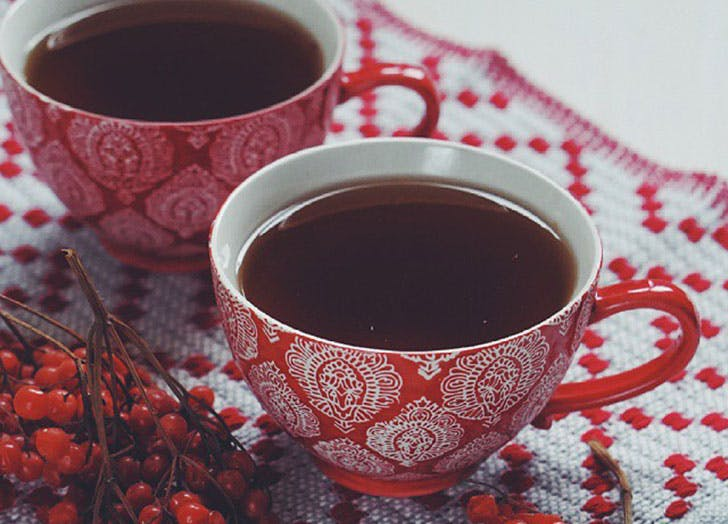 Cups of tea with red berries