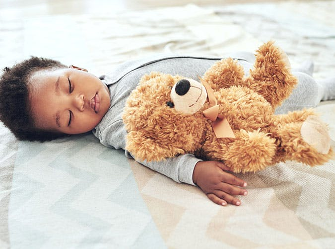Cute baby sleeping with teddy