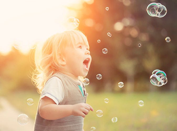 Cute toddler blowing bubbles