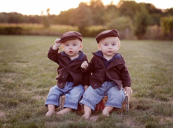 Two baby boys dressed up and sitting outside