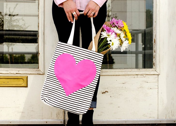 Woman holding a heart shaped tote bag