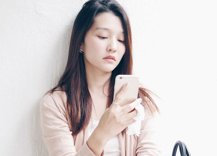 Woman looking sad and checking phone