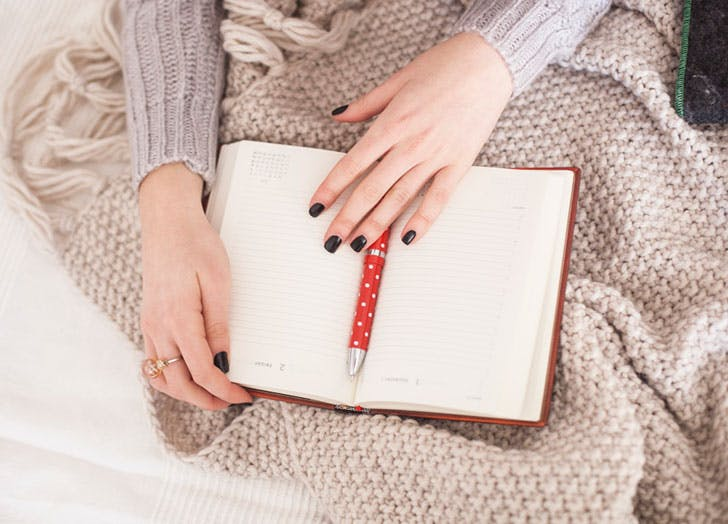 Woman writing in journal in bed