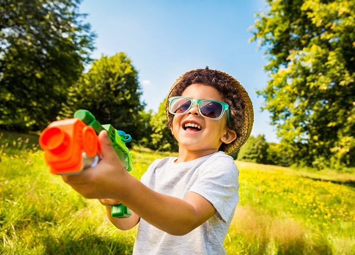 Young boy shooting water gun