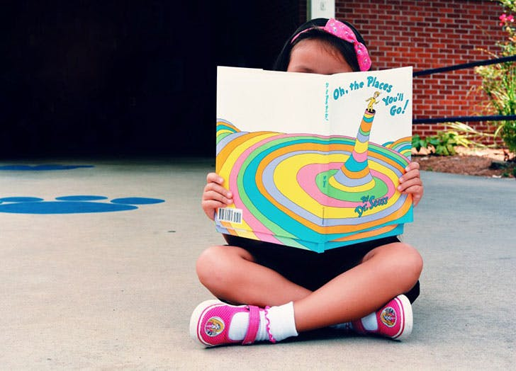 Young girl reading Dr Seuss book