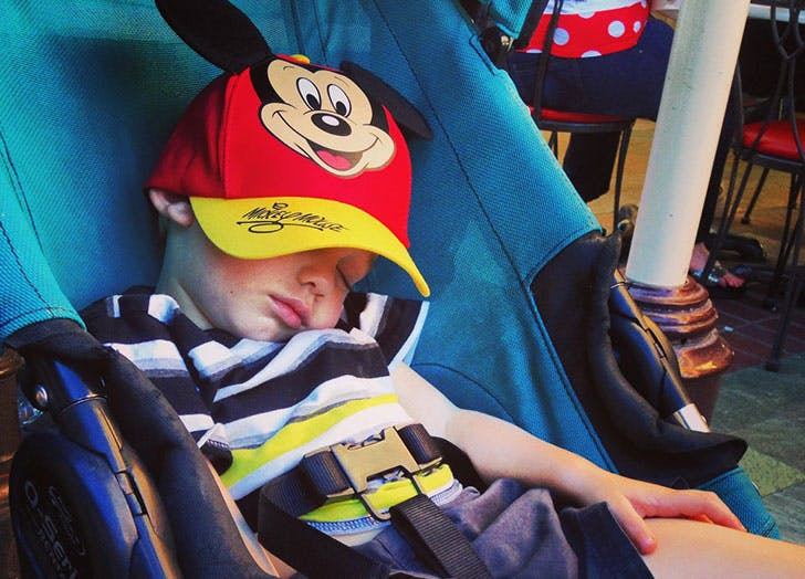 baby boy asleep in stroller with mickey ears on