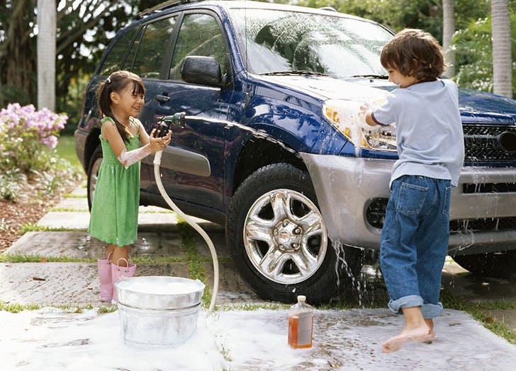 Two kids playing and washing the car