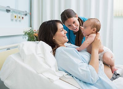 Woman holding her baby in hospital with a midwife next to her 400