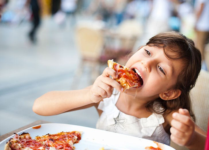 Young girl eating pizza at restaurant