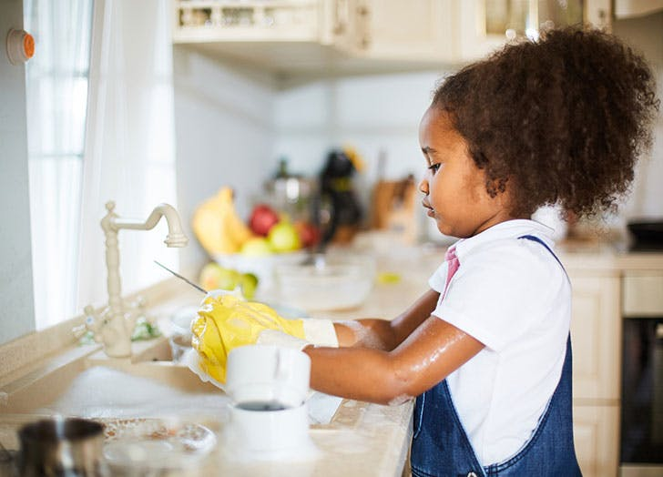 Young girl helping out and doing the dishes