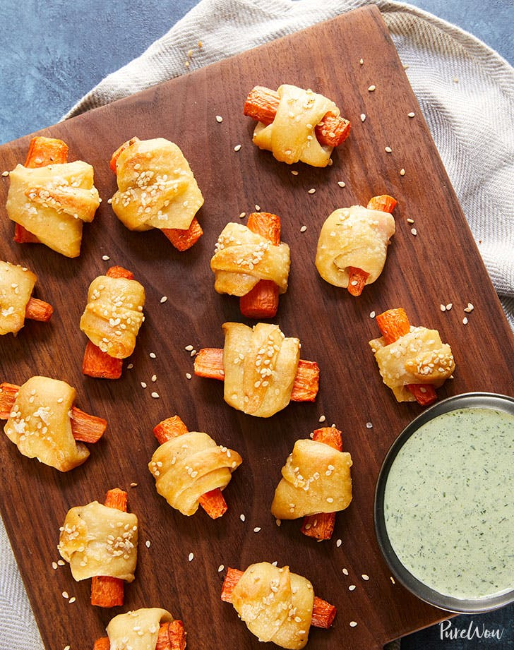 carrot pigs in a blanket on a wooden chopping board