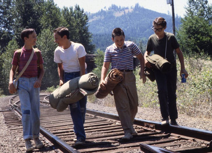 four boys crossing the railroad tracks in the family film Stand By Me