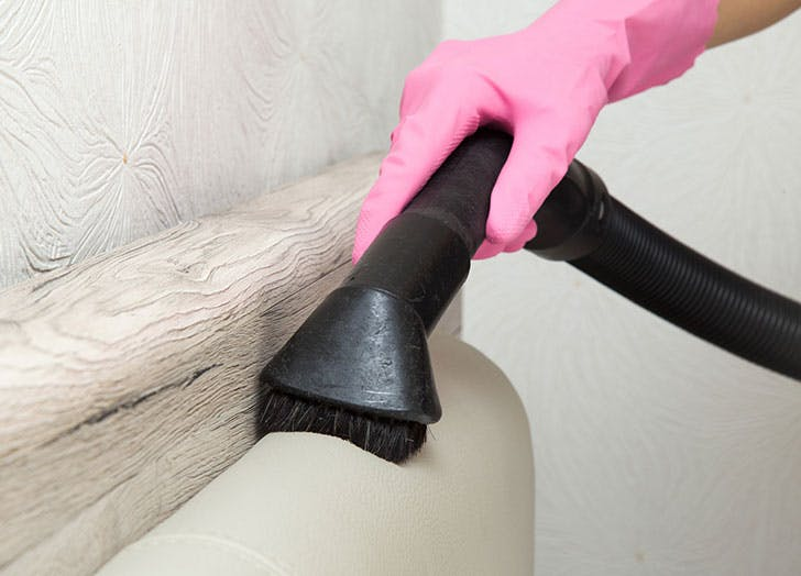 woman using upholstery brush to vacuum stairs