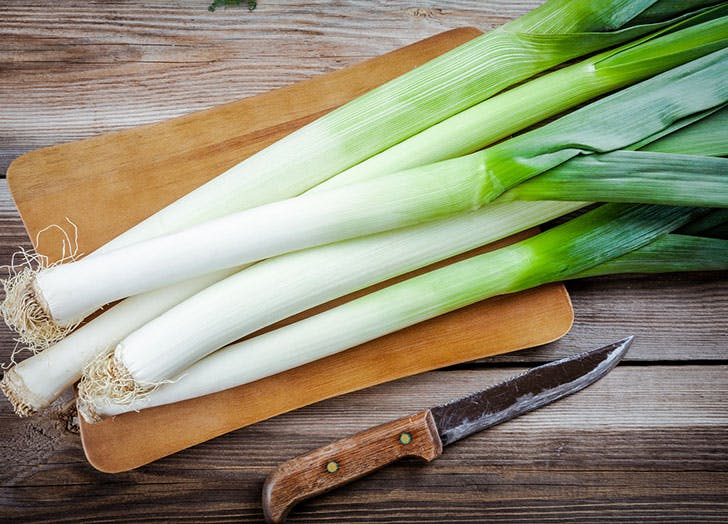 A bunch of leeks on wooden chopping board