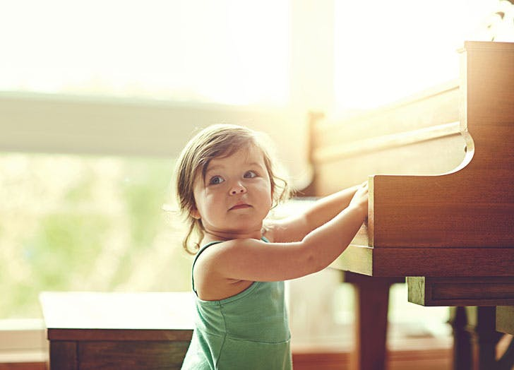 Adorable young girl playing the piano