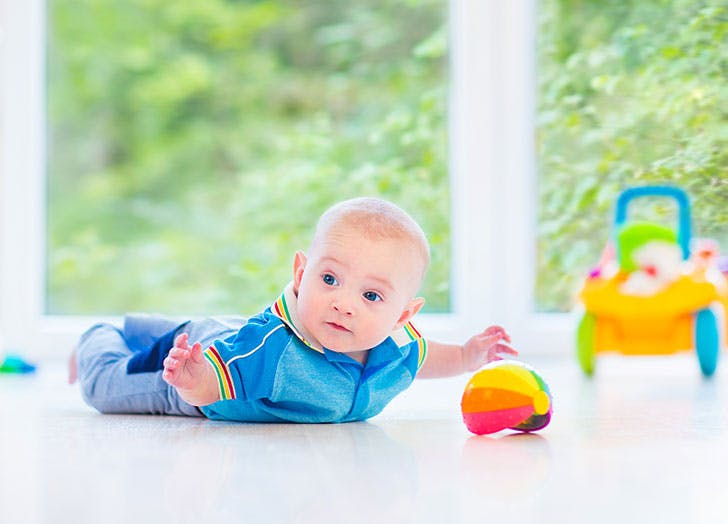 Baby boy on the floor doing tummy time with toys