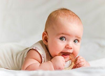 Baby girl lying on floor using a teething toy 400