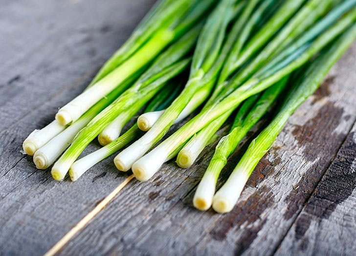Bunch of scallions on wooden board