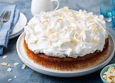 Coconut cake topped with lots of whipped cream 400