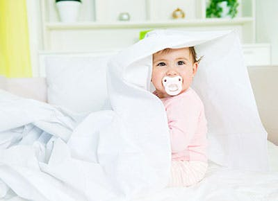 Cute baby girl in bed with pacifier in mouth 400
