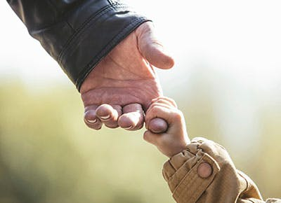 Small child holding the hand of a grandparent 400
