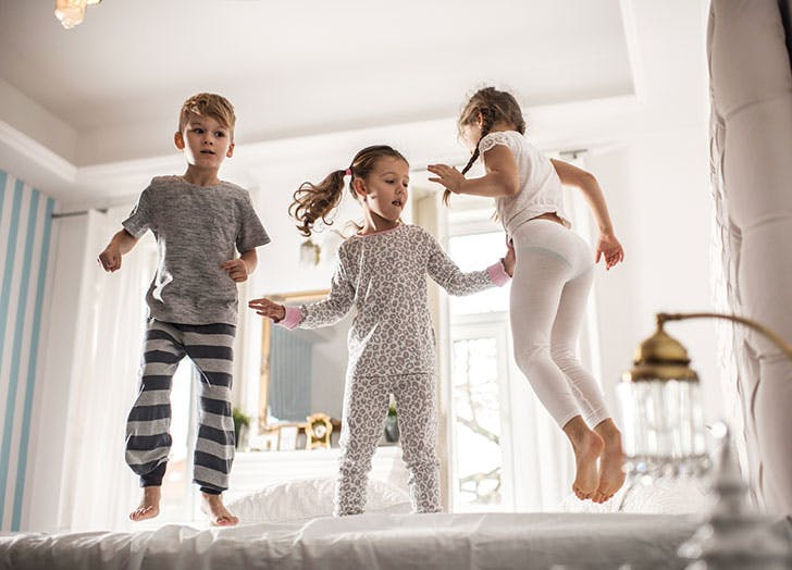 Three kids jumping on the bed