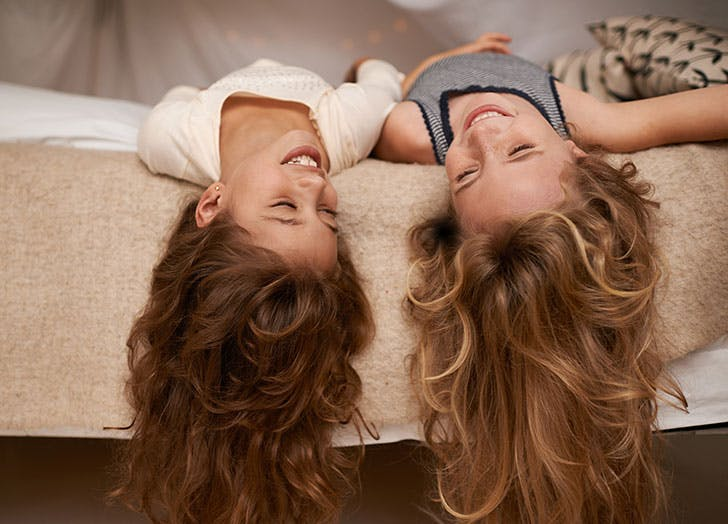 Two young girls laughing in bed