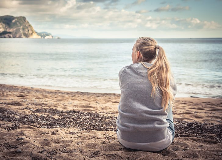 Woman sitting by herself on the beach looking out at water