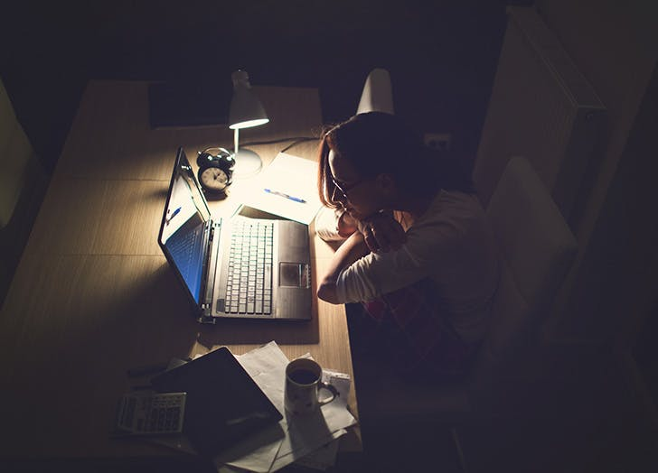 Woman working at desk with dim lighting