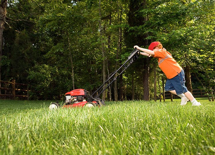 Young boy mowing the lawn