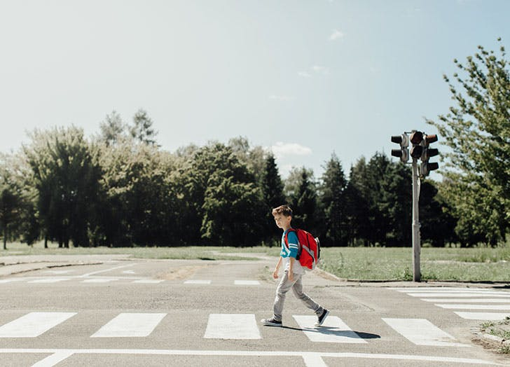 Young boy with backpack crossing the road to school