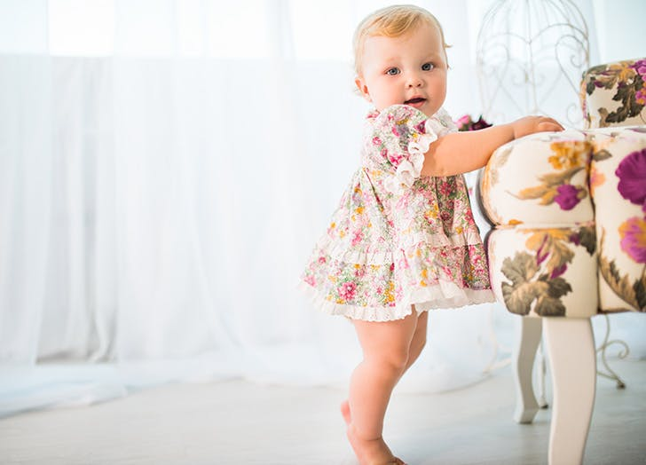 Cute baby girl taking her first steps