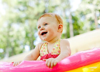 Cute red haired baby playing outside in pool 400