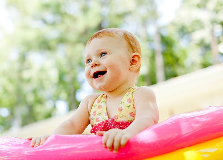 Cute red haired baby playing outside in pool