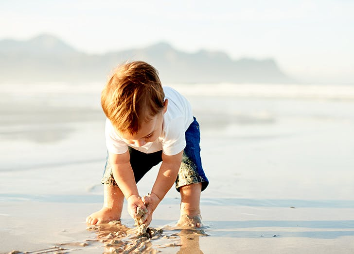 Cute red haired boy playing by the sea in the sand