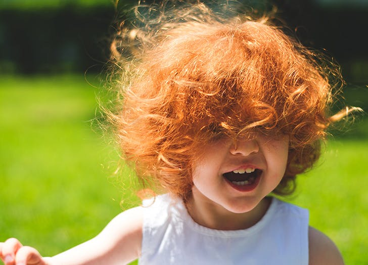 Cute red haired girl laughing outside