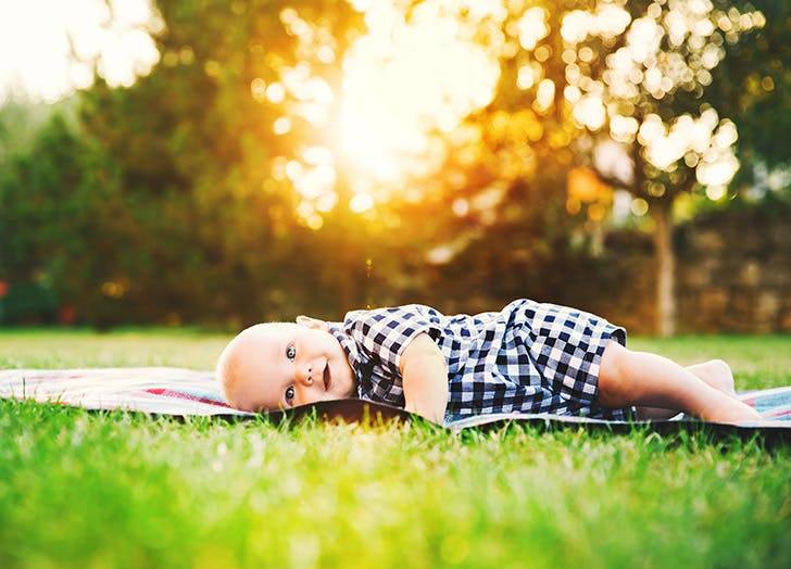 Happy adorable child baby boy lying on the grass and laughing in summer day on nature