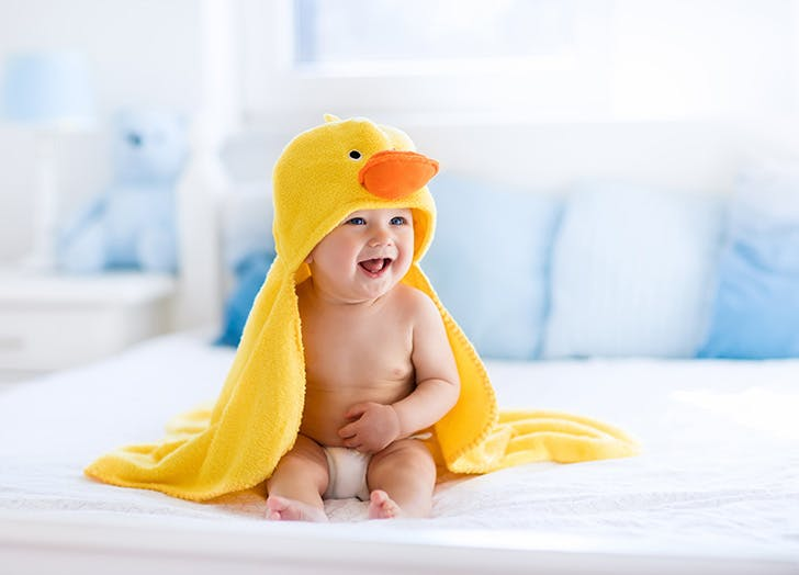 Little cute baby after bath in yellow duck towel