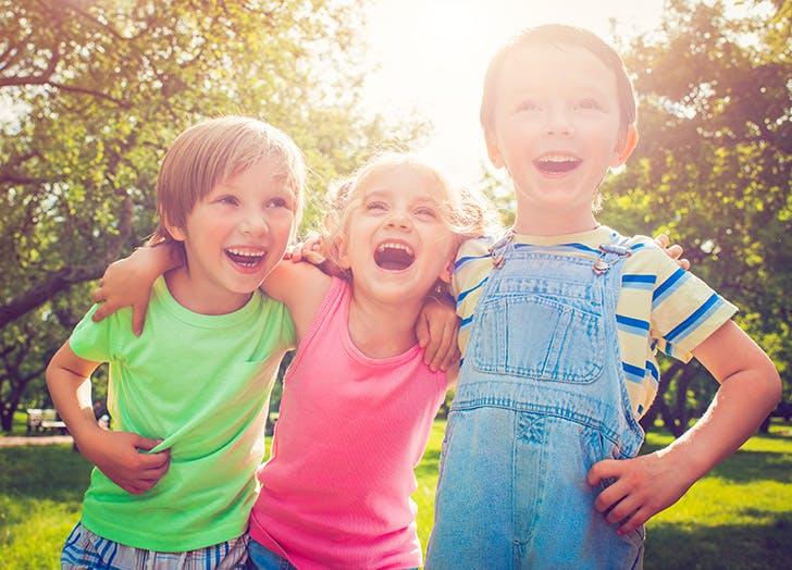Three cute kids laughing at a joke outside