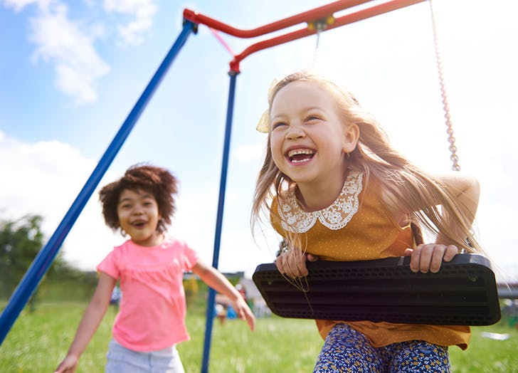 Two kids playing and laughing on swings