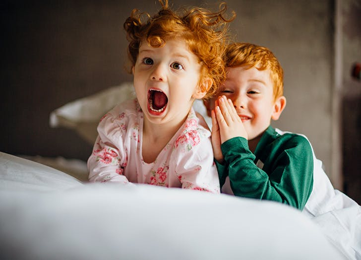 Two red haired siblings being silly on bed