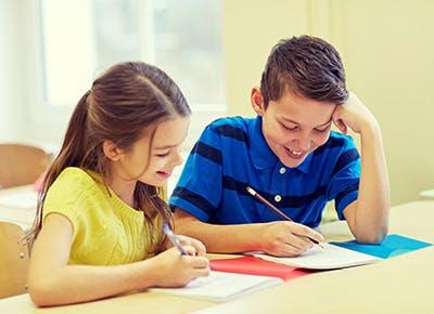 Two school kids writing test answers in school 400