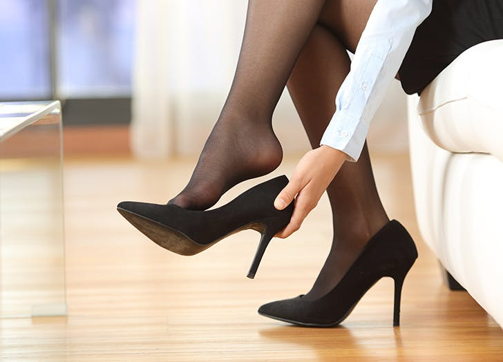 Woman removing her black high heeled shoes