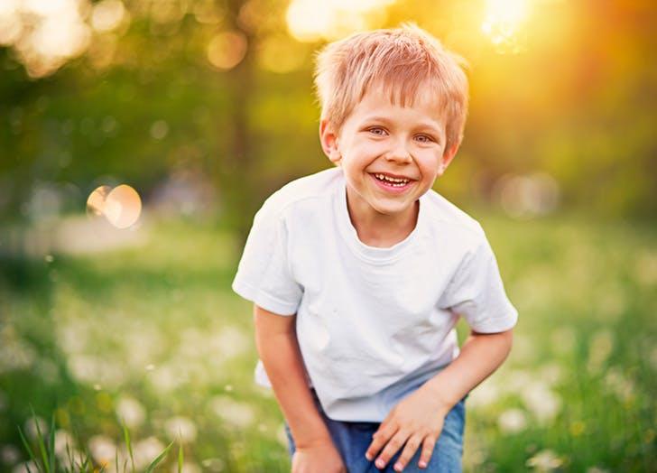 Young boy laughing at joke in dandelion field