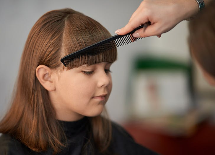 Young girl getting her hair cut