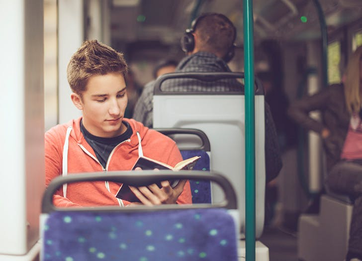 Young man on the subway reading
